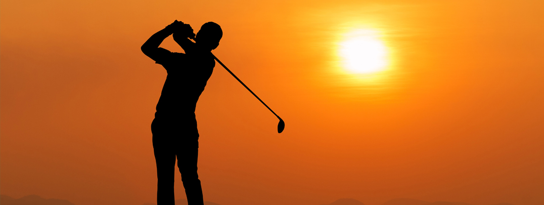 man golfing as the sun sets