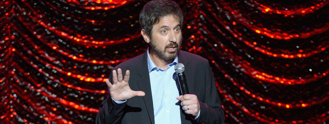 Ray Romano holds microphone on stage
