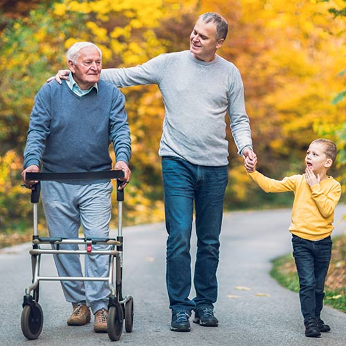 elderly patient walking with the help of a walker with son and granddaughter