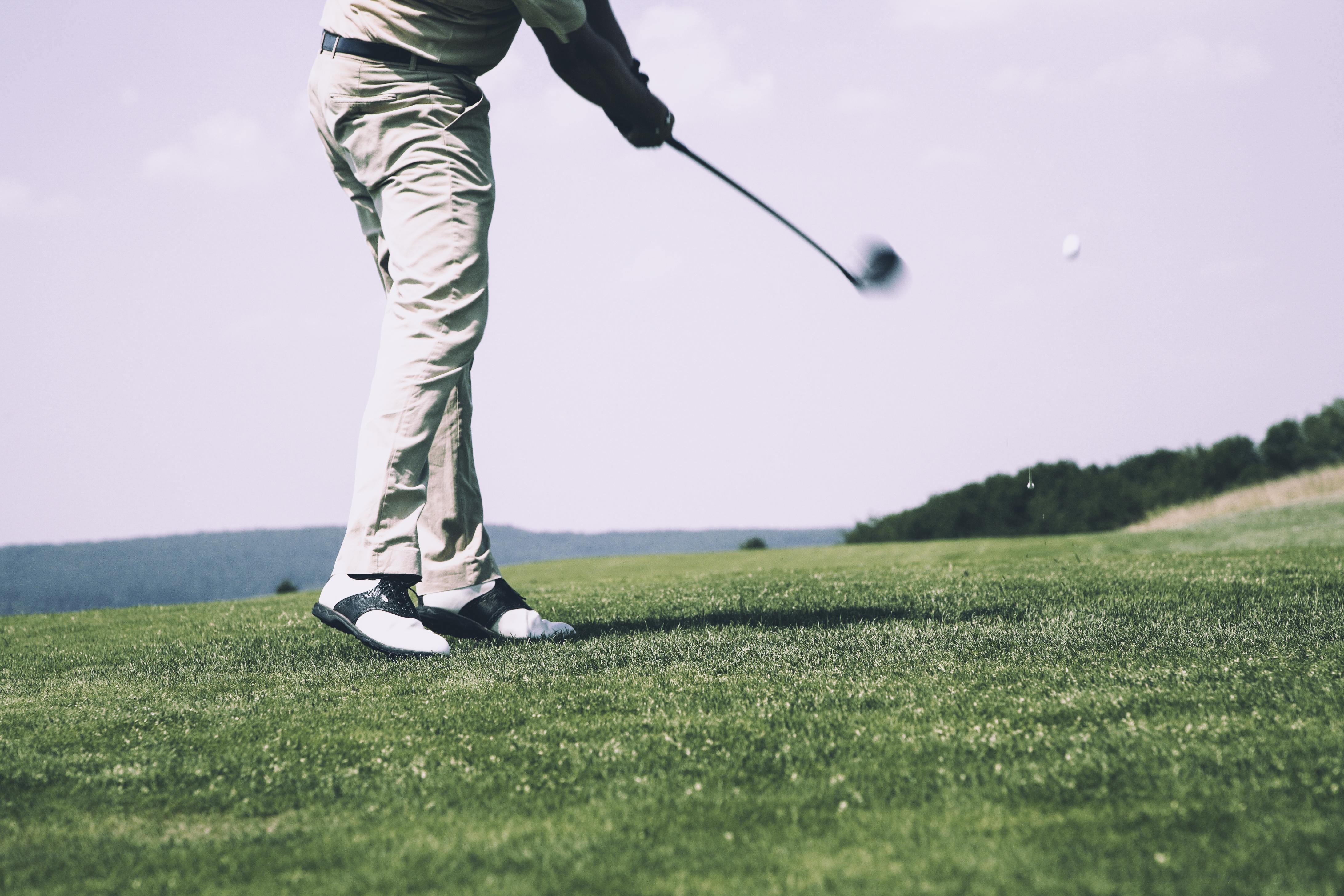 Golfer swings golf club on green