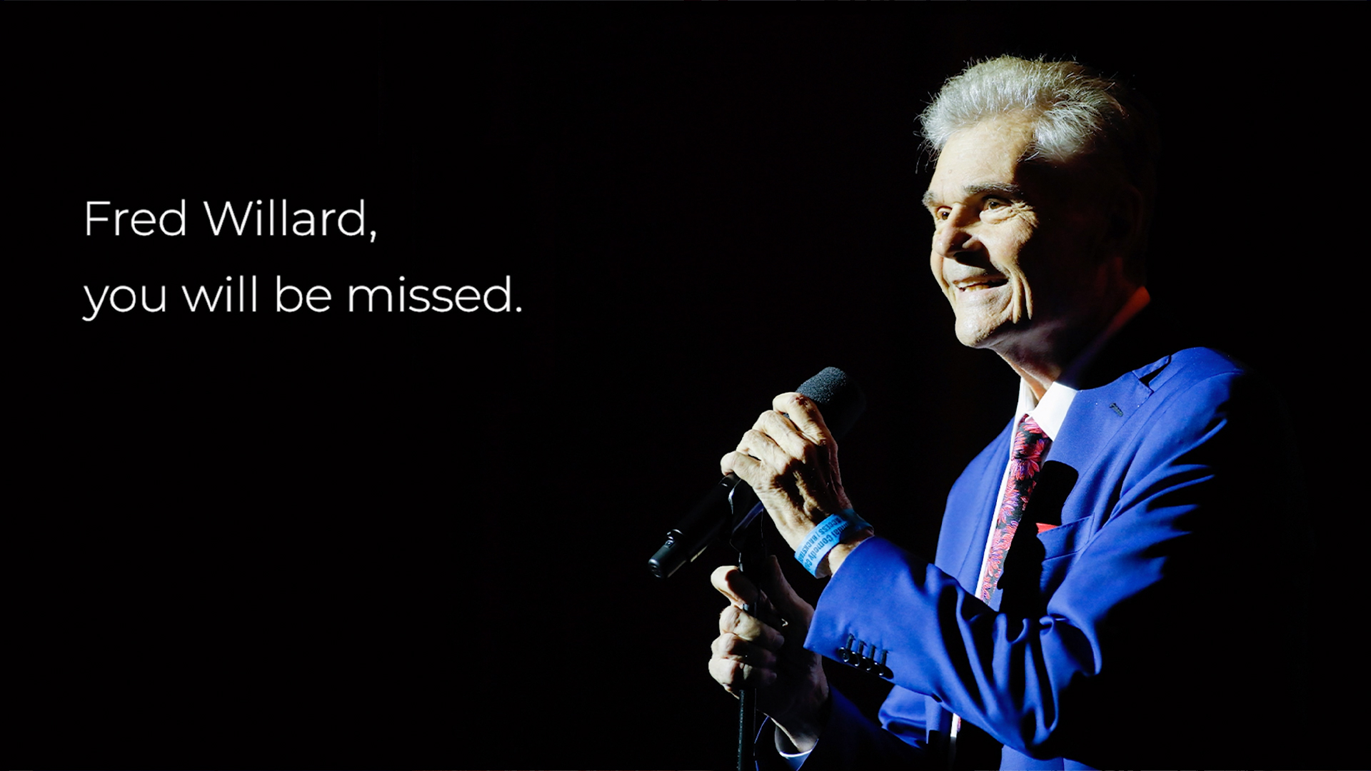 Comedian Fred Willard holds microphone