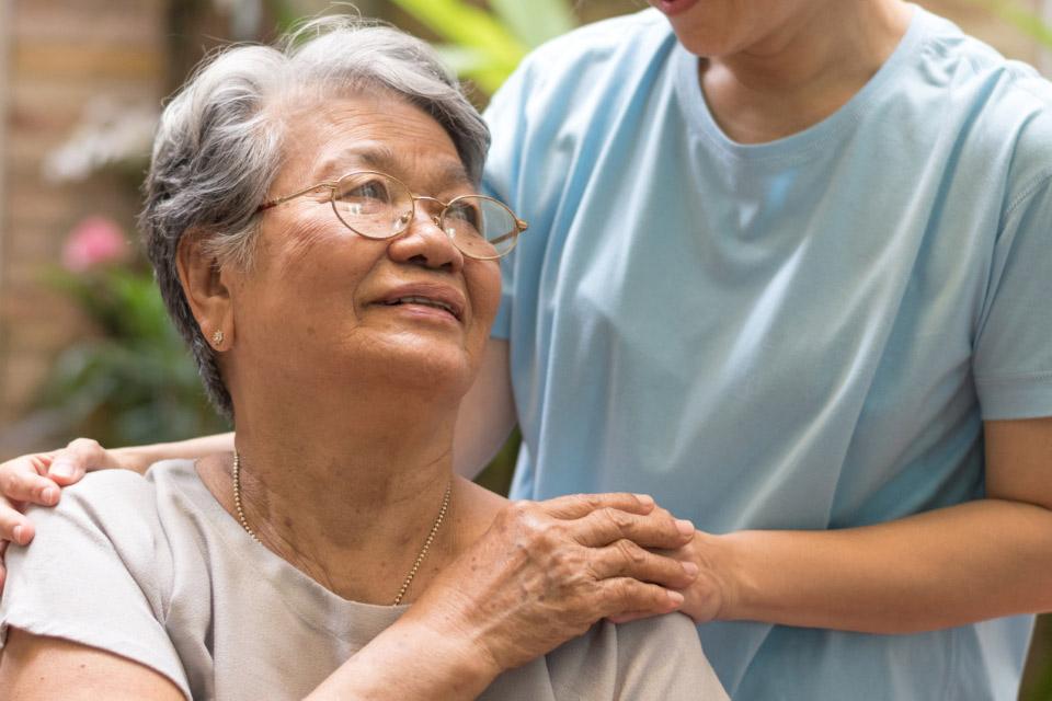 An Asian female senior citizen holds her caregiver's hand