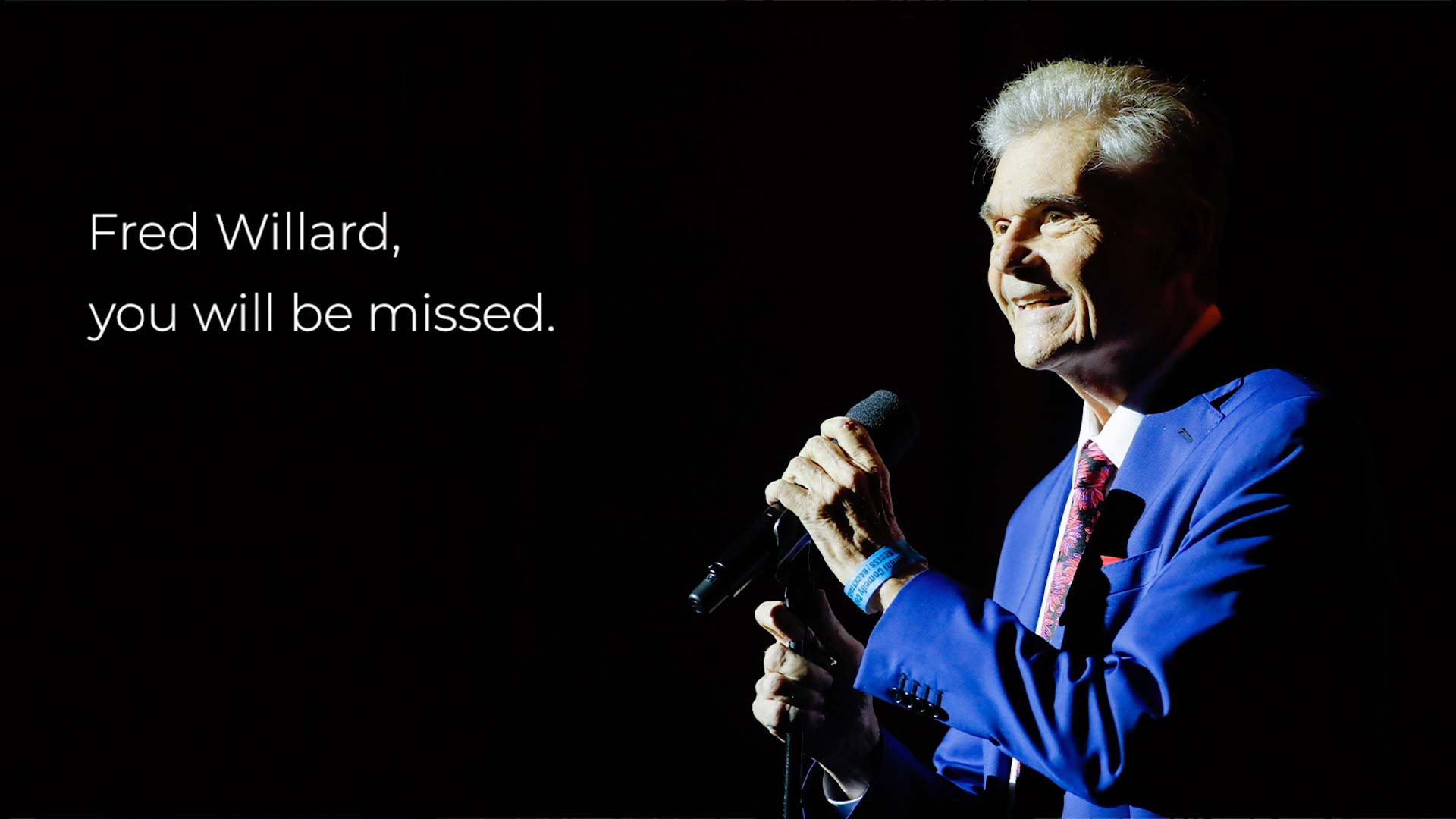 Comedian Fred Willard holds a microphone