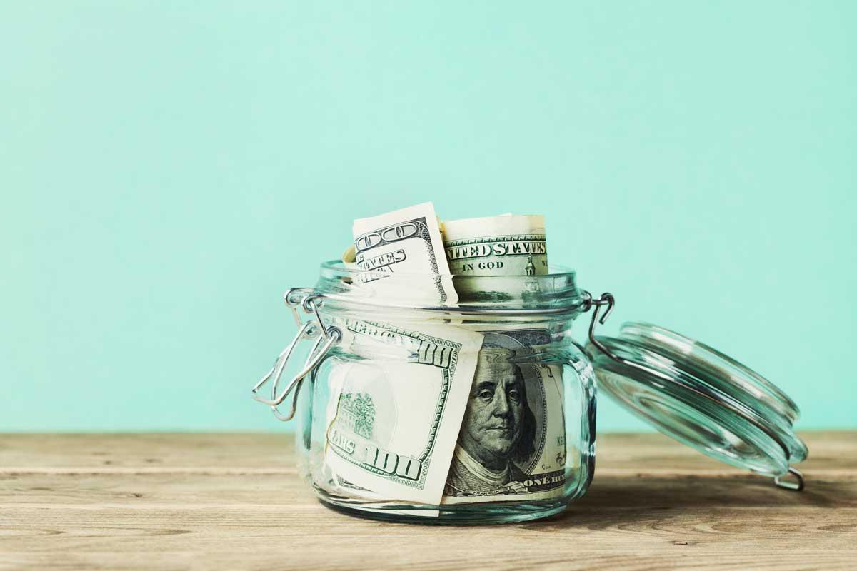 A jar filled with U.S. hundred dollar bills