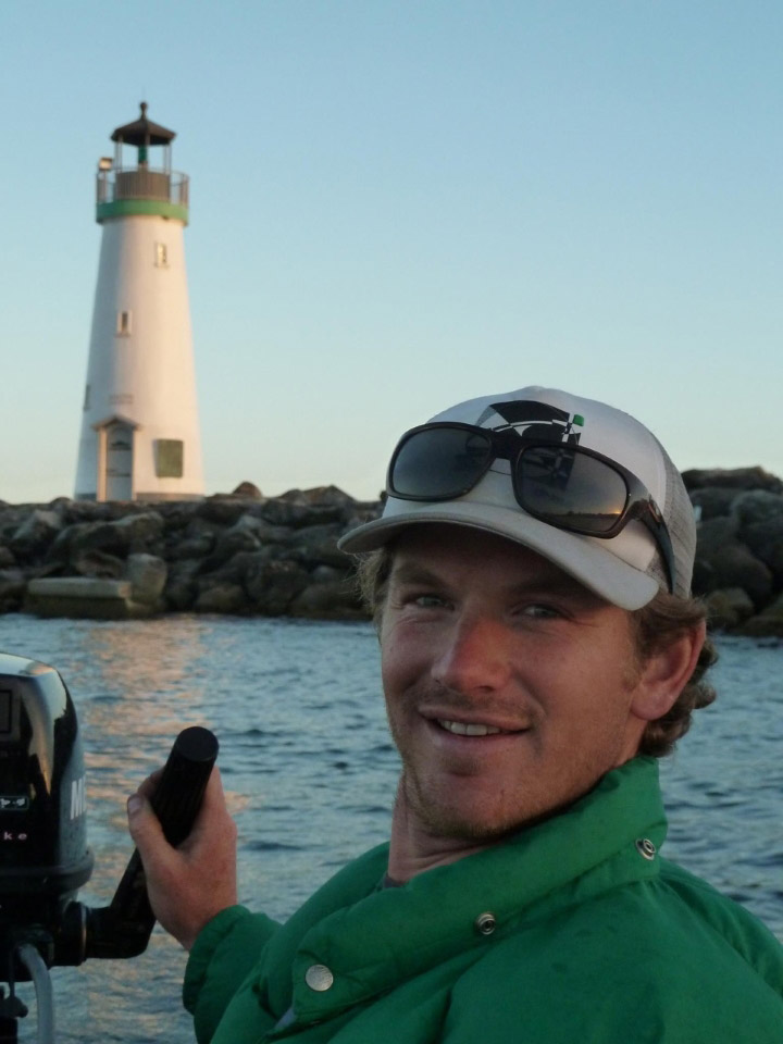 John Taussig steers a boat by a lighthouse