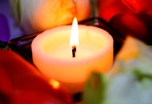 A lit candle surrounded by flower petals