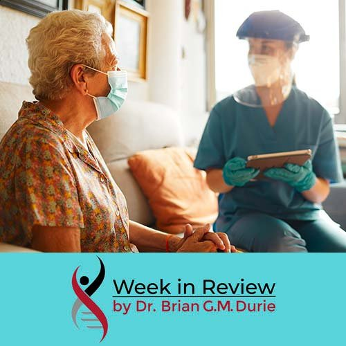 An elderly myeloma patient sits down with a doctor who is outfitted in full PPE protection