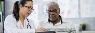 A doctor gives a patient a medical pamphlet during his doctor visit
