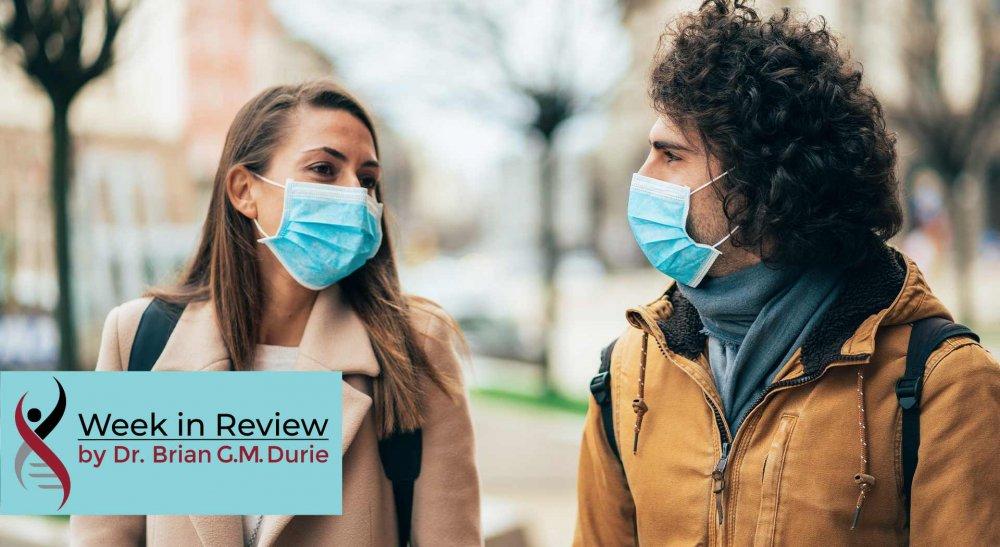 A couple talk outside while wearing masks