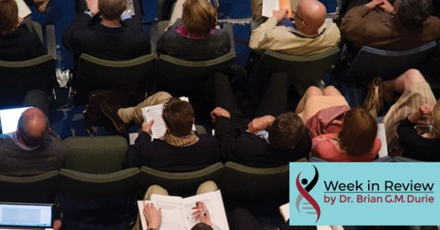 Overhead view of people sitting in chairs taking note