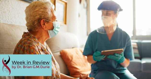 An elderly patient visits with a doctor equipped with full PPE protection