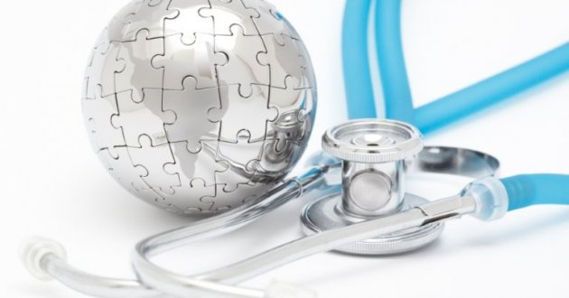 Silver dome made of puzzle pieces next to a blue stethoscope on a blue background