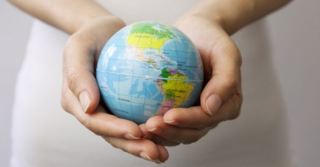 A globe held in a person's hands.