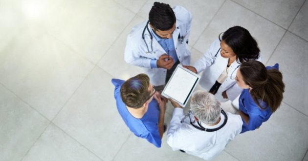 Overhead view of medical staff looking at an ipad