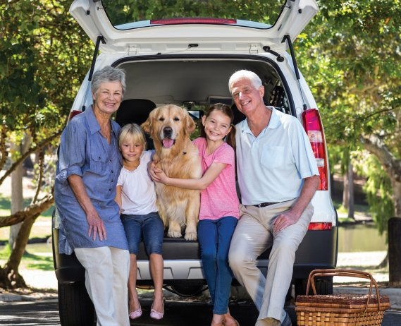 family sitting on trunk of van