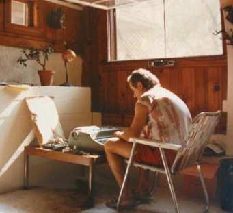 Brian Novis hunched over a typewriter in his garage