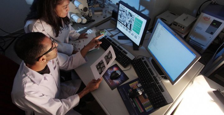 Two researchers look at computer screen