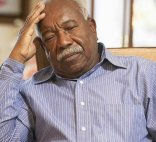An older African-American man sits with a worried expression