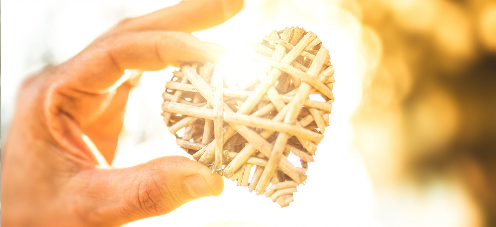 A hand holds a wooden woven heart