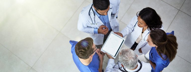 a group of medical researchers circle up around an ipad in a lobby