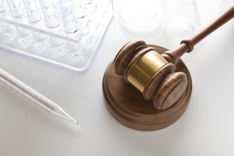 Judge's gavel along side medical research test tubes