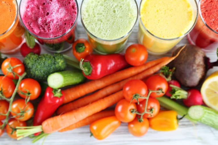 Colorful fruit smoothies and assorted vegetables