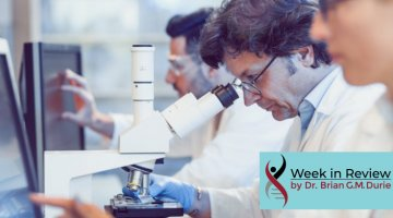 People in lab researching, looking at computer screens and microscope