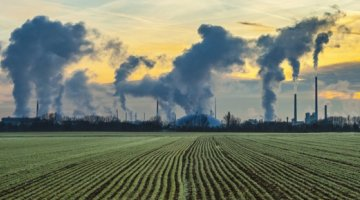 CO2 bi products entering air from smoke stacks next to a field of crops.