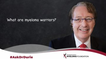Video still of Dr. Brian G.M. Durie with chalkboard backdrop and text overlay: What are myeloma warriors?