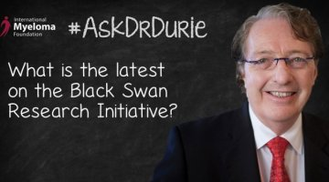 "Video still of Dr. Brian G.M. Durie  against chalkboard backdrop with text overlay of ""What is the latest on the Black Swan Research Initiative?"""