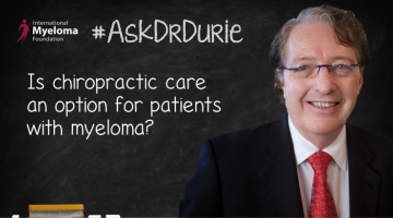"""Video Still of Dr. Brian G.M. Durie with chalkboard backdrop and text overlay: """"Is chiropractic care an option for patients with myeloma?"""""""