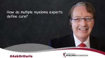 Dr Durie infront of a blackboard with the words how do myeloma experts define cure