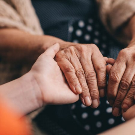 young hands hold older persons hands